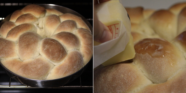 Hand rubbing stick of butter over baked bread to make it shiny