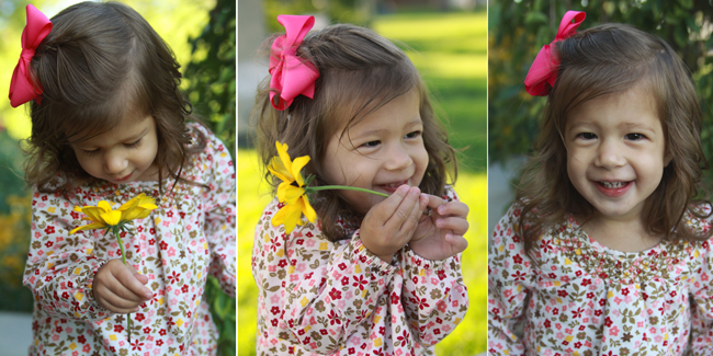 A little girl holding a flower and smiling