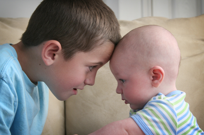 A young boy sitting near a baby