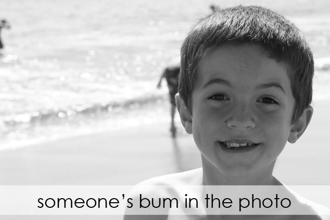 photo of a boy at the beach with another little boy right behind his head