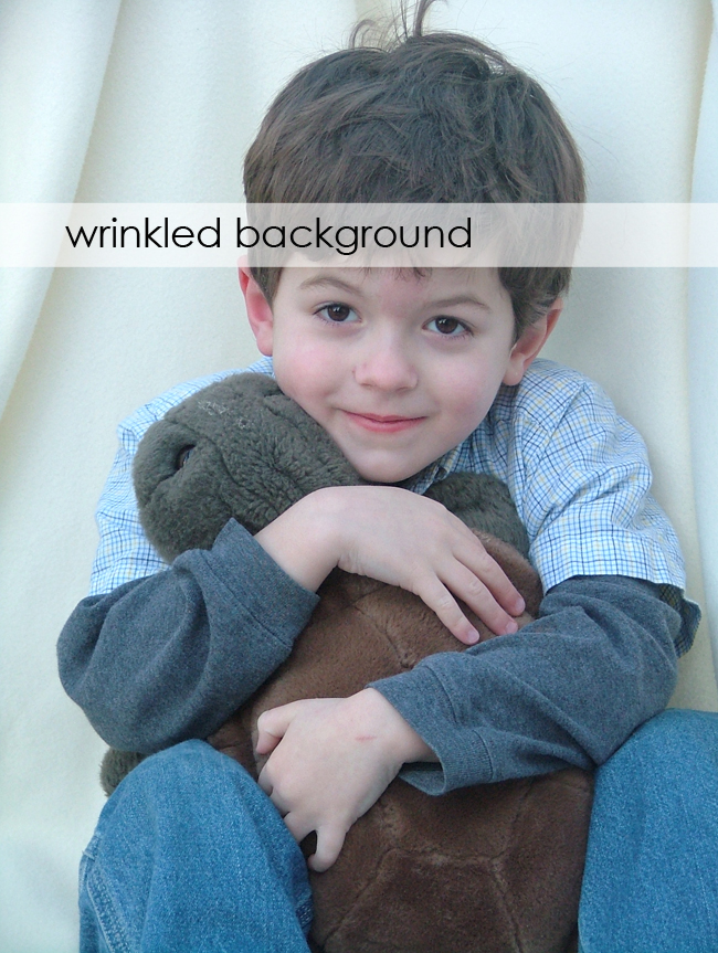 A little boy holding a teddy bear with a wrinkled blanket background
