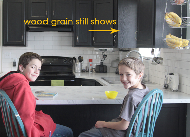 kids in a kitchen where cabinets were painted black