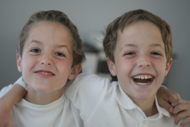 A close up of two young boys laughing