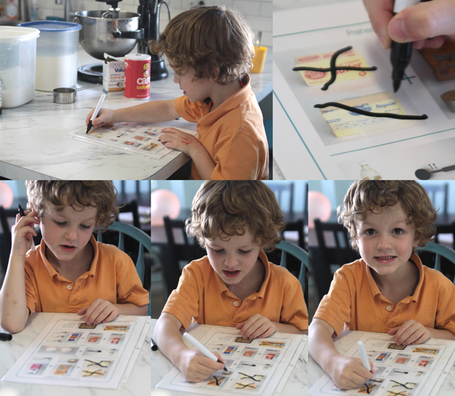 A boy marking off ingredients on illustrated cookie recipe sheet