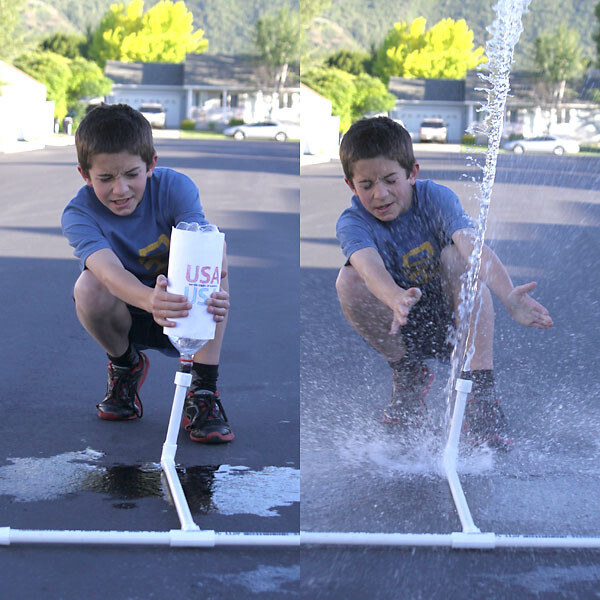little boy holding a 2 liter bottle decorated to look like a rocket on a pvc pipe; bottle has shot off and spray of water coming from pipe
