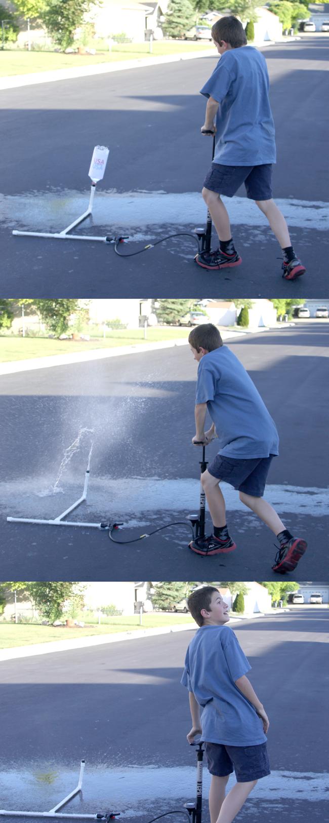little boy using bike pump to create pressure inside pvc pipe rocket launcher