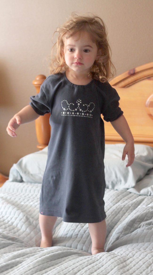 A little girl standing on a bed in an upcycled nightgown