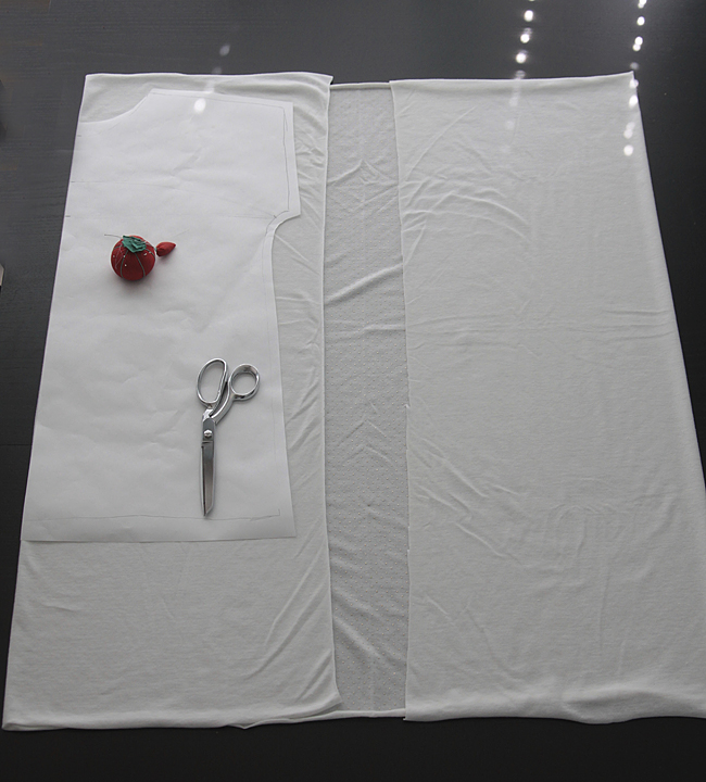 Shirt pattern laid over white knit fabric, with pin cushion and sewing scissors