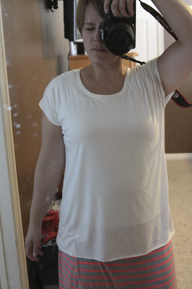 A person standing in front of a mirror wearing a handmade t-shirt taking a selfie