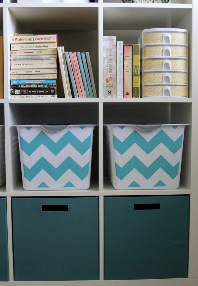 A close up of a cube storage unit with white bins that have been covered with turquoise chevron fabric