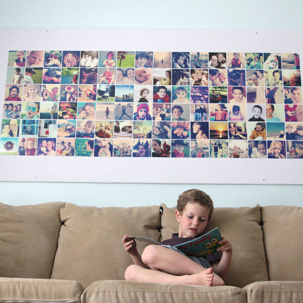 A young boy sitting on a sofa in front of a giant bulletin board covered with photos