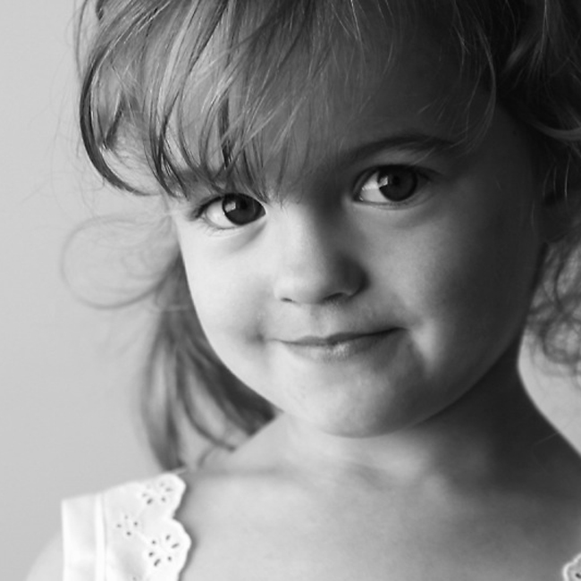a well lit black and white photo of a little girl