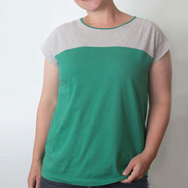 A person in a t-shirt that's grey across chest and shoulders and green on the lower portion
