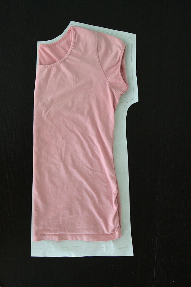 Pink t-shirt folded on paper, traced around to create a pattern