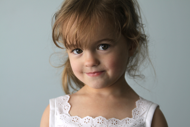 A little girl posing for a picture wearing a lace trimmed blouse