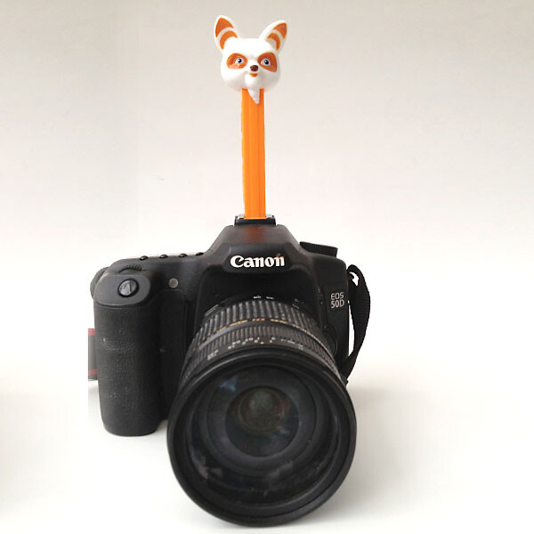 A close up of a camera with a pez dispenser attached on top