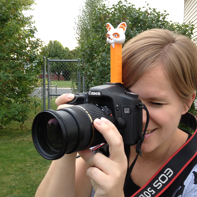 A woman holding a camera with a pez dispenser attached on top