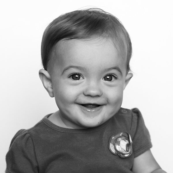 A black and white photo of a baby smiling
