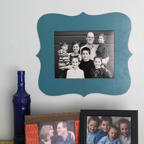 A black and white family photo in a blue scalloped frame
