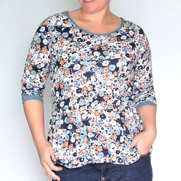A woman wearing a floral peplum top with long sleeves