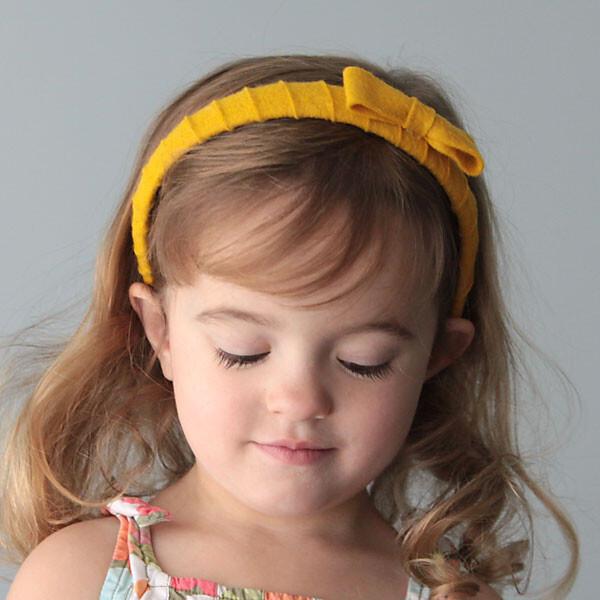A girl wearing a yellow felt wrapped headband