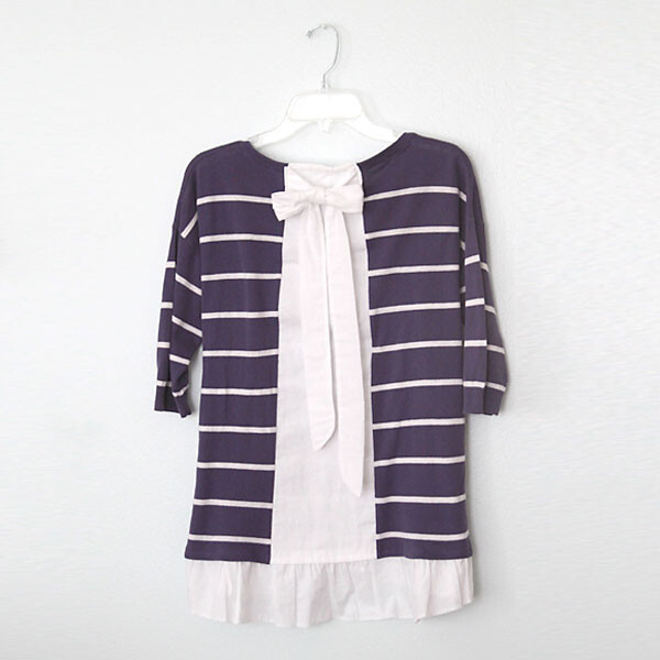 A purple striped sweater with white ruffled hem and bow in the back