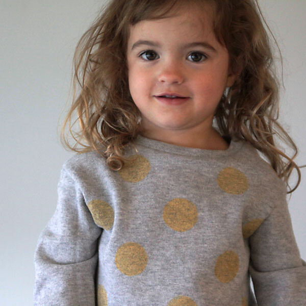 A little girl wearing a grey sweatshirt with gold polka dots