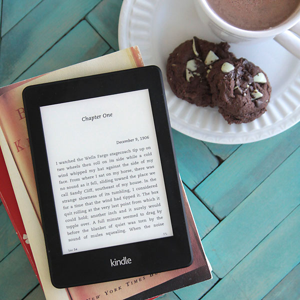 A kindle on a stack of books on a tray with cookies and cocoa