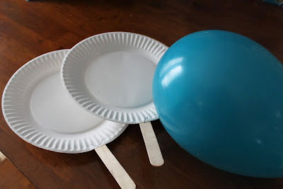 A blown up balloon and two paddles made from paper plates and popsicle sticks
