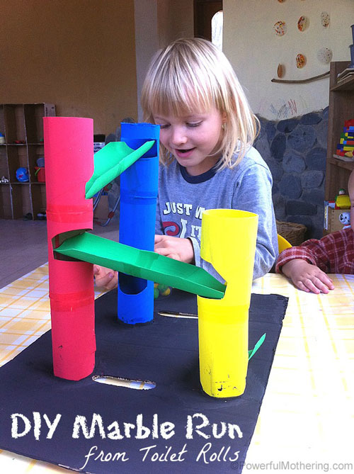 A girl playing with a track made from cardboard tubes