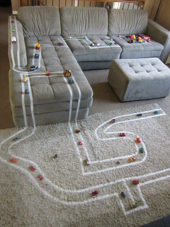 A living room with a car track made out of masking tape all over the couch and carpet