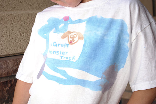 A young boy in t-shirt with his drawing on it
