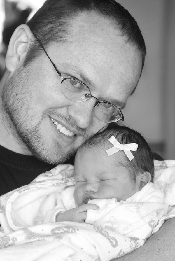 black and white photo of a dad snuggling his newborn baby