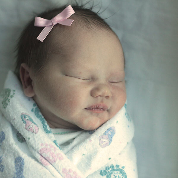 newborn baby girl wrapped up in a blanket
