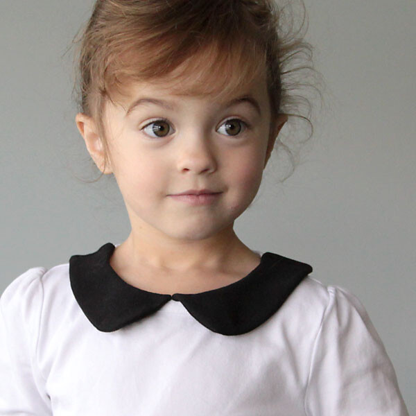 A little girl in a white shirt with a black peter pan collar