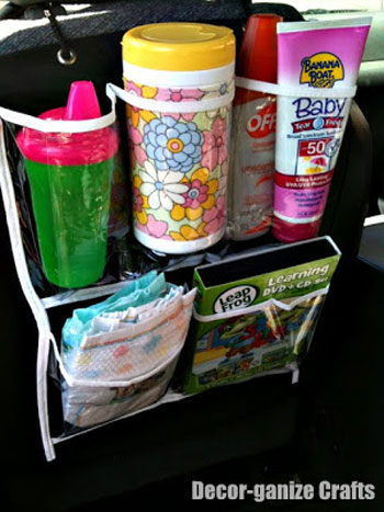 A shoe organizer on the back of a car seat with a sippy cup, wipes, sunblock, and diapers in it