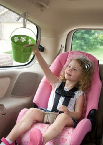 A little girl sitting in a car seat reaching for a bucket that hangs in front of her