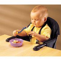 A baby sitting in a high chair that attached to a table