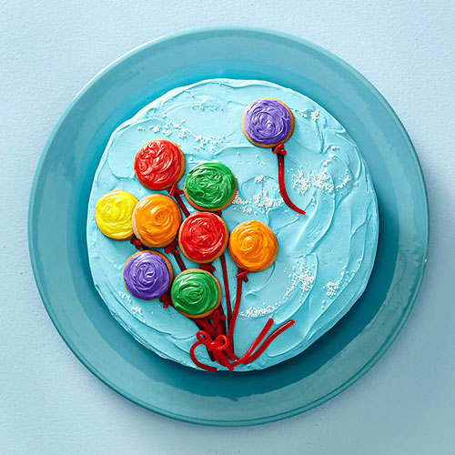 A birthday cake with blue frosting and balloons made from frosting cookies on it