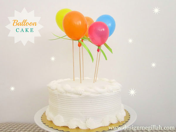 A birthday cake with tiny balloons on skewers sticking out of it