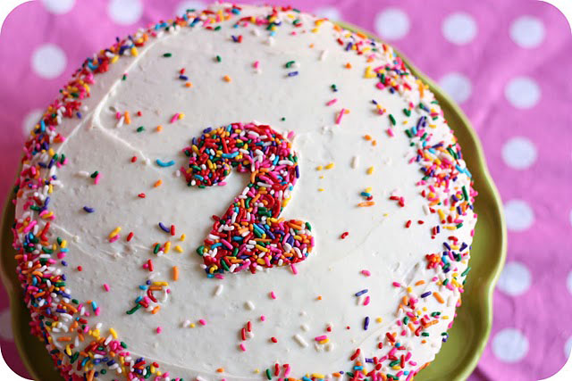 A close up of a birthday cake with the number 2 on it in sprinkles