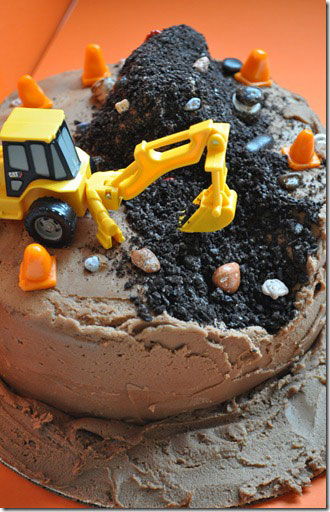 A large chocolate cake with a toy digger on top and pieces of the cake crumbled away