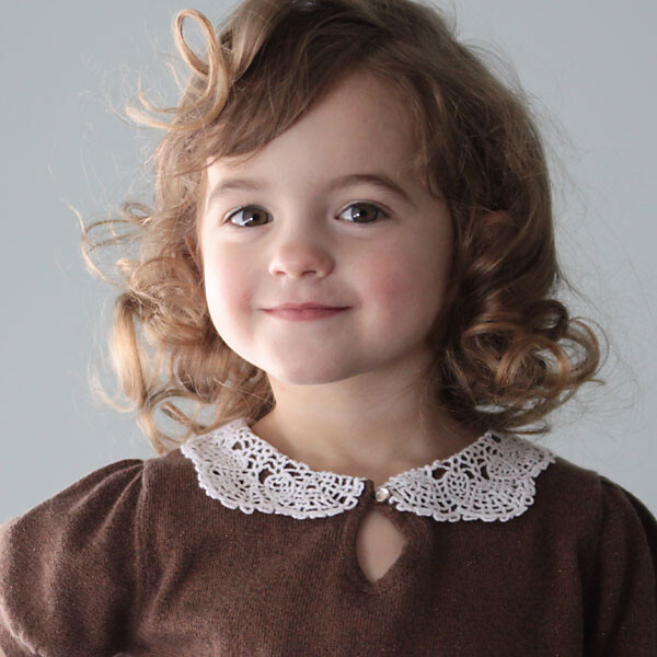 A little girl wearing a brown shirt with a doily collar