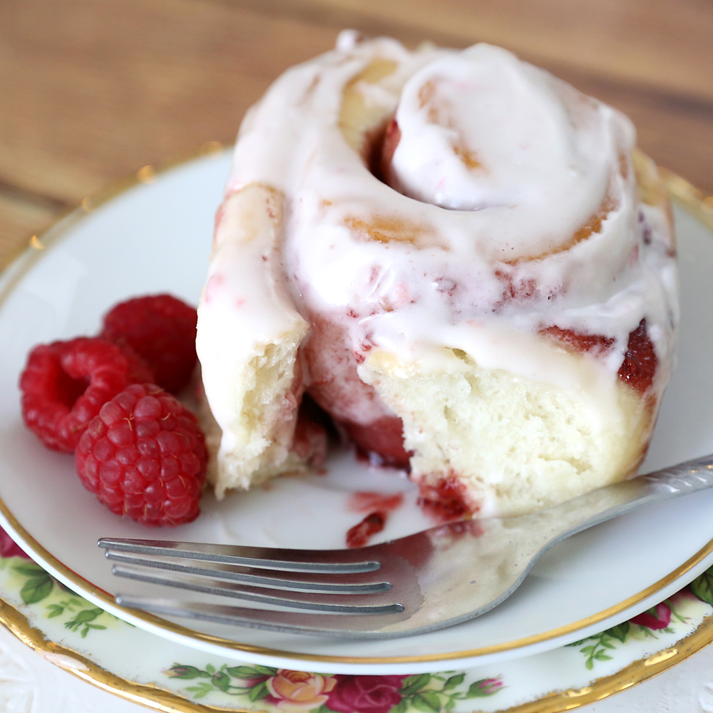 A raspberry sweet roll with cream cheese frosting on a plate