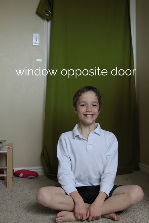 Little boy sitting in a bedroom with green curtain panel hanging on a door behind him