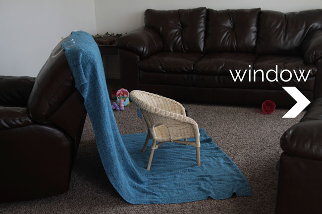 A wicker chair set up across from a window with a blue blanket draped behind it
