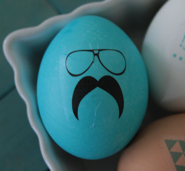 Blue Easter egg with glasses and mustache design