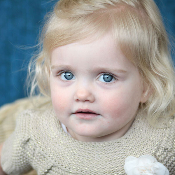 A close up of a baby girl with a blue background