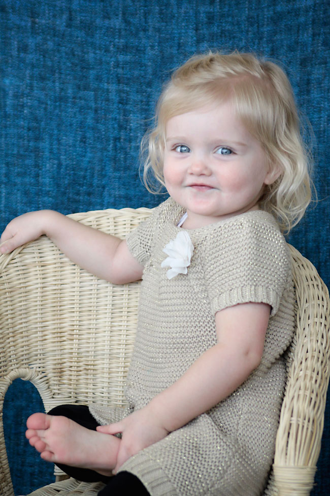 A little girl in a wicker chair smiling