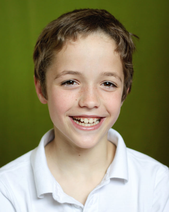 A young boy who is smiling at the camera in front of a green background